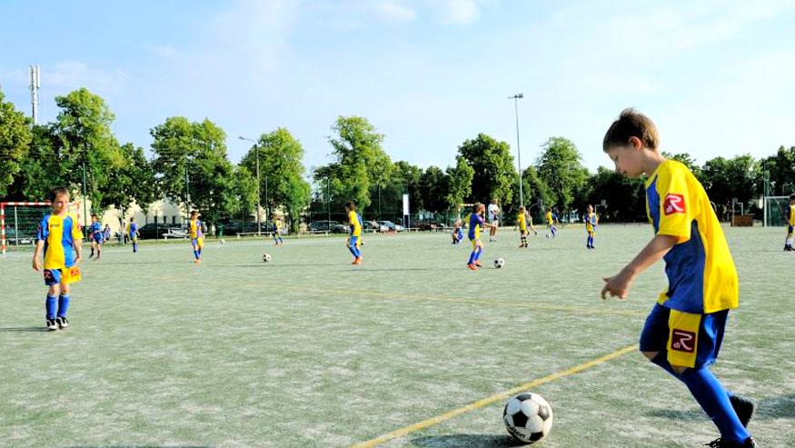 Młodzież grająca w piłkę na sztucznym boisku