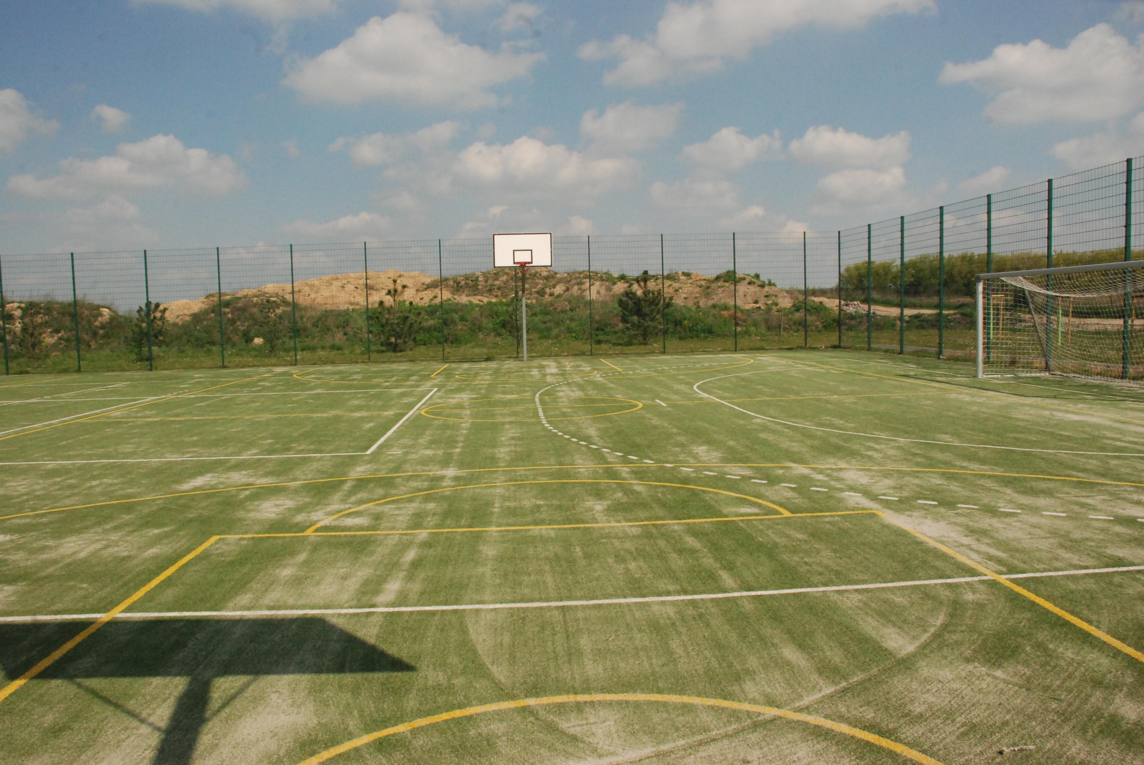 Boisko ze sztuczną nawierzchnią w Zielątkowie. Widok boiska do koszykówki. Na skraju boiska znajduje się bramka do piłki nożnej