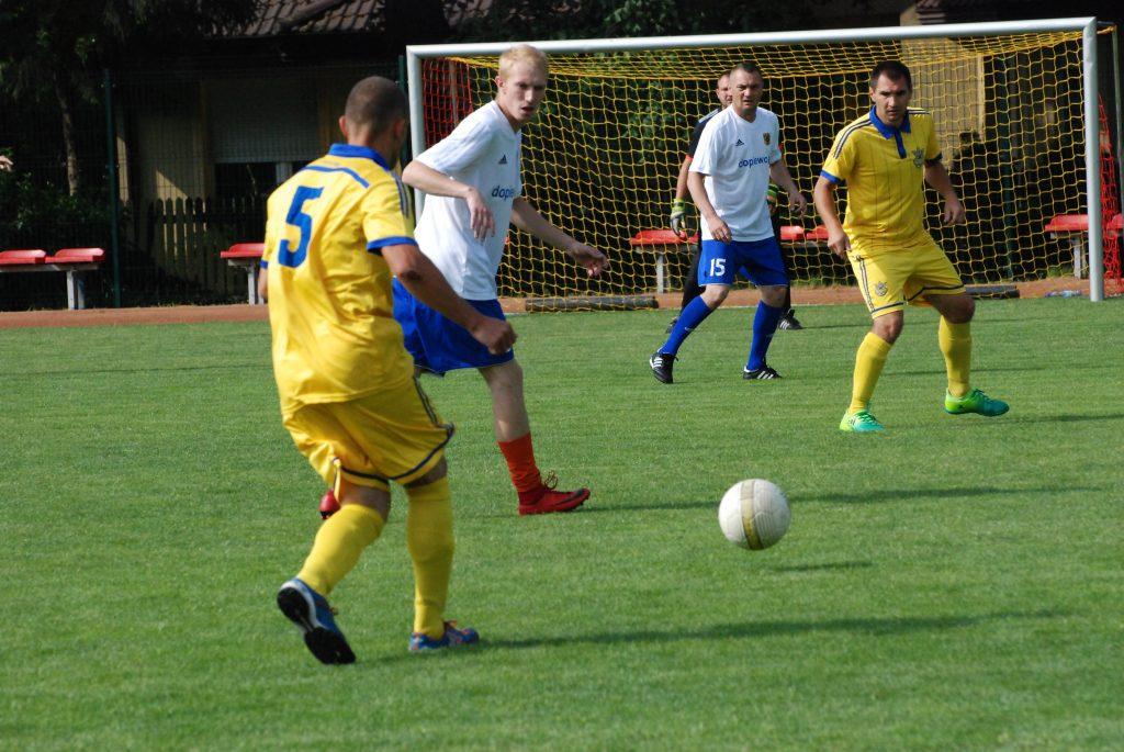 Zawodnicy grający w piłkę na naturalnej murawie